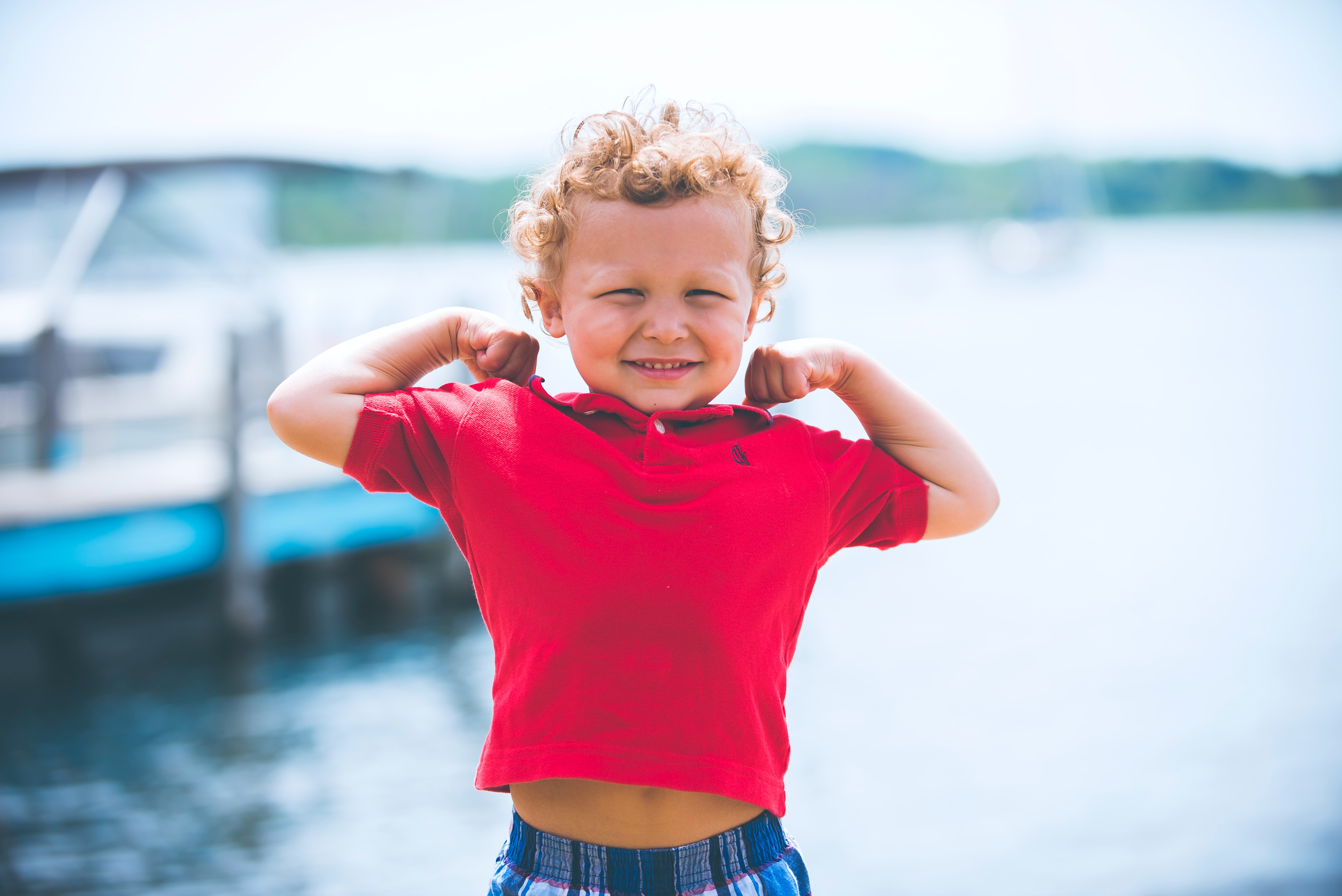 little boy in red shirt showing strength; pre-employment assessment